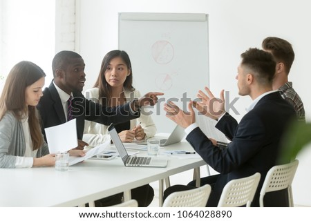 Diverse employees arguing during team meeting, african office worker disagreeing with caucasian colleague, black and white businessmen disputing at negotiations, multiracial conflict at work concept