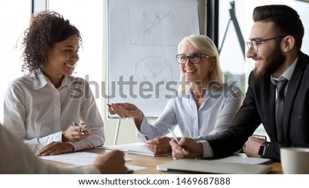 Diverse employees business partners discussing ideas at briefing in boardroom, brainstorm, African American businesswoman and Caucasian businessman listening to mature team leader at meeting
