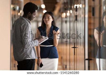 Diverse employees discussing project in modern office hallway, African American businessman and Asian businesswoman talking, colleagues having business conversation in corporate work space corridor