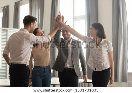 Diverse employees team giving high five, workers group celebrating successful deal, great business result at briefing, engaged in team building activity, motivated for better teamwork result
