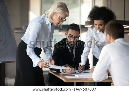 Diverse employees team working on project together, analyzing statistics, report, business negotiations in boardroom, colleagues discussing startup ideas during briefing, business meeting