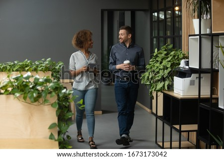 Diverse employees walking in modern office, chatting during break, discussing project or sharing news, Caucasian businessman and African American businesswoman having pleasant conversation