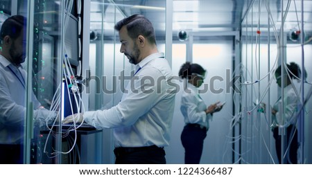 Diverse engineers work in the server room in the data center with cables #1224366487