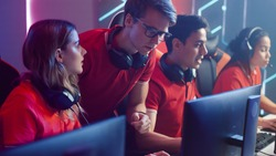 Diverse Esport Team of Pro Gamers Play in Video Game on a Championship, Talking Using Headsets, Trainer Explains Strategy. Stylish Neon Cyber Games Arena. Online Tournament Event