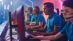 Diverse Esport Team of Pro Gamers Playing in Video Game on World Championship, use Headsets to Talk. Stylish Neon Cyber Games Arena. Online Broadcasting of Tournament Event