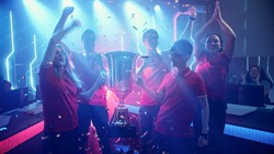 Diverse Esport Team Winner of the Video Games Tournament Celebrates Victory Cheering and Holding Trophy in Big Championship Arena. Cyber Gaming Event with Gamers and Fans.