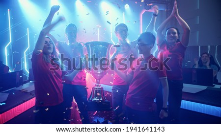 Diverse Esport Team Winner of the Video Games Tournament Celebrates Victory Cheering and Holding Trophy in Big Championship Arena. Cyber Gaming Event with Gamers and Fans. Photo stock ©