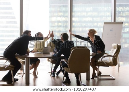 Diverse executive business team give high five in office, international corporate staff group colleagues businesspeople celebrating good teamwork, company success, professional leadership victory