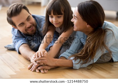 Diverse family married couple little adorable daughter lying at cushion on warm floor play smiling feels happy hold stack hands, close up. Touching arms gesture of support, love and closeness concept