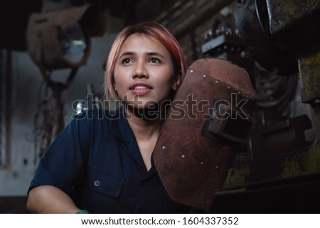 Diverse female industrial engineer holding welding helmet after work shift - Young Asian factory metal worker taking a break - Hispanic apprentice woman learning new skills on internship training Foto stock ©