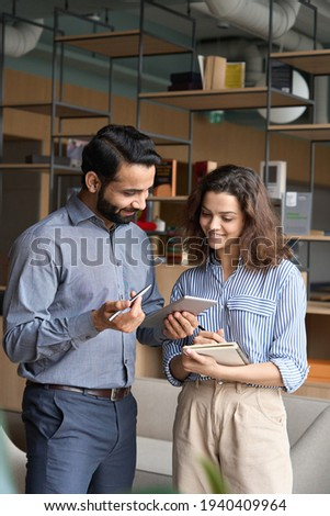 Diverse friendly coworkers talking using digital tablet in office. Indian manager having discussion with latin employee meeting in office lobby discussing project, teaching new employee sharing ideas.