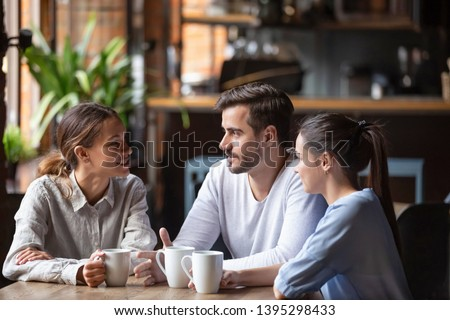 Diverse friends chatting, drinking coffee, sitting together in cozy cafe, friendly people enjoying pleasant conversation at coffee break, man telling story from life, feeling happy and satisfied