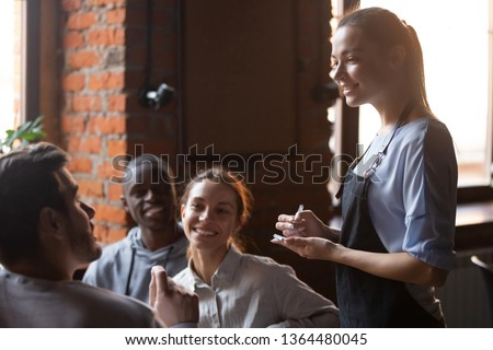 Diverse friends gathered together sitting in cafe talking with worker service waiting staff place make order food drink, young waitress business owner listening client wishes writing list in notepad