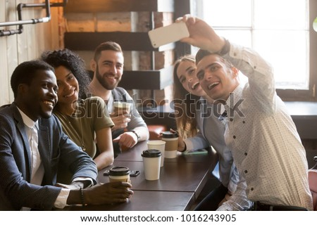 Diverse friends making selfie on smartphone together in cafe, young man holding phone shooting video or taking photo on mobile of african and caucasian millennial people sitting at coffee shop table #1016243905