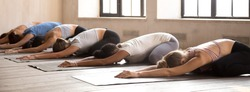 Diverse girls energize start new day with yoga session. Sportive females lying resting on rubber mats doing Child Pose, side view. Horizontal photography banner for website header. Wellness concept