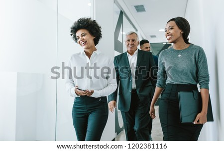 Diverse group of business people walking through office corridor.  Team of corporate professionals walking and talking in modern office hallway.