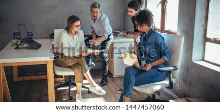 Diverse group of business people working together at a small office. Woman showing her digital tablet and discussing new business plan with coworkers.
