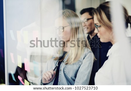 Diverse group of businesspeople standing together in a modern office brainstorming with sticky notes on a glass wall