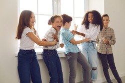 Diverse group of children playing, tickling each other and laughing during break at school or fun party at home. Happy childhood, social interaction with peers, intercultural kids community concepts
