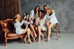 Diverse group of female friends enjoying at a party and laughing. Group Of beautiful women having fun and Sitting on Sofa. Ladies in white clothes