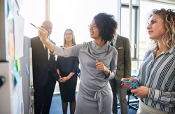 Diverse group of focused businesspeople brainstorming together on a whiteboard during a strategy session in a bright modern office
