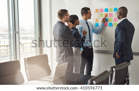 Diverse group of four business people gathered around white board with sticky notes planning something