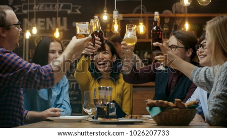 Diverse Group of Friends Celebrate with a Toast and Clink Raised Glasses with Various Drinks in Celebration. Beautiful Young People Have Fun in the Stylish Bar/ Restaurant.