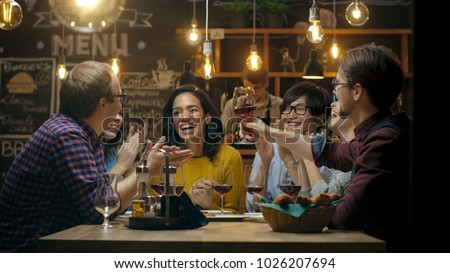 Diverse Group of Friends Celebrate with a Toast and Raise Wine Glasses in Celebration. Beautiful Young People Have Fun in the Stylish Bar/ Restaurant. #1026207694