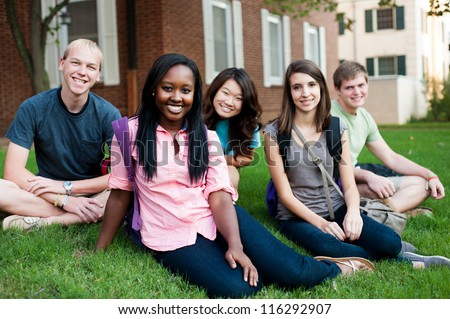 Diverse group of friends outside sitting on a lawn