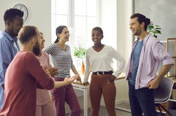 Diverse group of happy cheerful friends meet and have fun together. Bunch of positive young multiracial people standing in office or living-room, talking, sharing news and funny stories and laughing