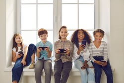 Diverse group of happy 9-10 year old children playing online games on cell phones. Smiling boys and girls holding mobile devices and looking at camera sitting on windowsill with white mockup window