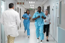 Diverse group of male and female doctors running through busy hospital corridor. medicine, health and healthcare services.
