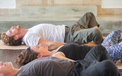 Diverse group of people on wooden floor practicing yoga lying in Reclined Butterfly exercise relaxing after practice. Healthy lifestyle concept