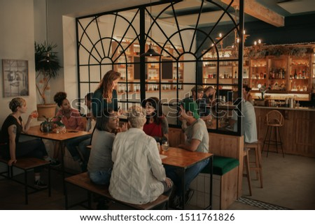 Diverse group of smiling friends ordering from a waitress while sitting in a bar together at night
