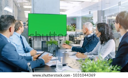 Diverse Group of Successful Business People in the Conference Room with  Green Screen Chroma Key TV on the Wall.  They Work on a Company's Growth, Share Charts and Statistics. #1031044369