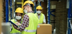 Diverse group of warehouse workers wear protective face mask to prevent COVID-19 infection working and doing inventory in storehouse together. warehouse and inventory concept.