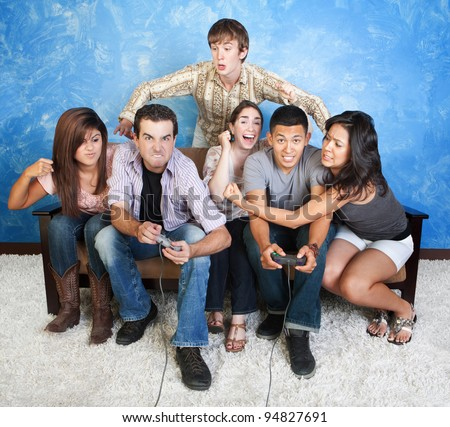 Diverse group of young people fight over video games