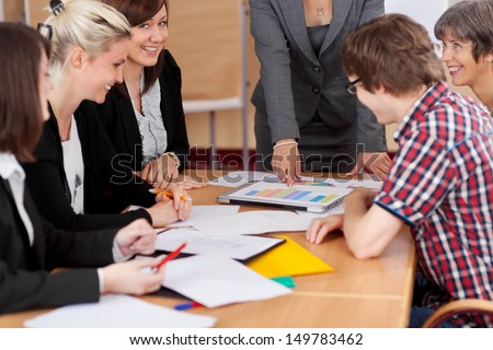 Diverse group pf young business people seated round a table discussing graphs in a business meeting