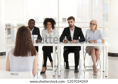 Diverse HR managers listen to female job candidate speaking during work interview in office, multiethnic recruiters consider woman candidature at hiring. Recruitment, employment concept