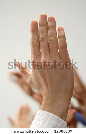 Diverse human hands up in a vote or in a questioning gesture
