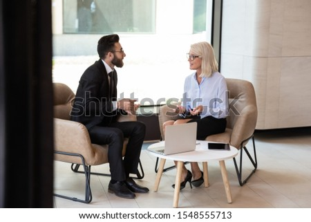 Diverse international man and woman business partners talk discussing potential cooperation, multiracial colleagues businesspeople speak consider project or idea at office meeting, partnership concept