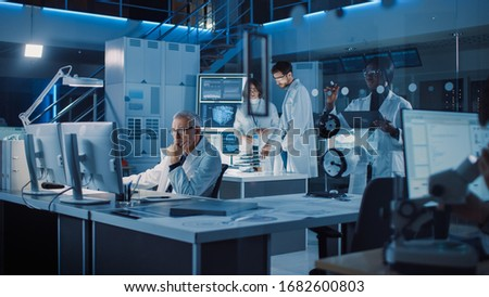 Diverse International Team of Industrial Scientists and Engineers Wearing White Coats Working on Industrial Machinery Design in Research Laboratory. Professionals Using Computers and Talking
