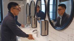 Diverse men washing hands in washroom sink of business center or restaurant