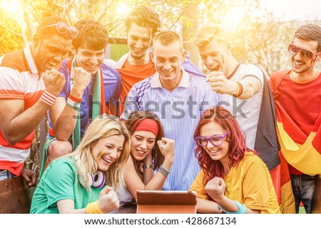 Diverse mix of friends sports fans watching football match on tablet outdoor - Celebrating winning goal huddled on couch shouting excited - Sport against racism concept - Main focus on blond girl #428687134