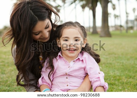 Diverse mom and daughter sitting in the grass