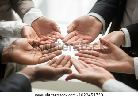 Diverse multi-ethnic business team members join helping hands group together palms up as concept of involvement, contribution in common goal, supporting unity and crowdfunding donation, close up view #1022451730
