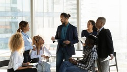 Diverse multiethnic businesspeople gather at casual meeting in office, brainstorm over business project together. Multiracial colleagues talk discuss company financial paperwork. Teamwork concept.