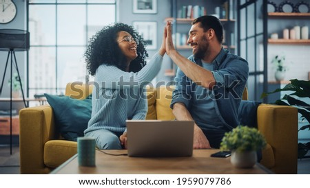 Diverse Multiethnic Couple are Sitting on a Couch Sofa in Stylish Living Room and Choosing Items to Buy Online with Laptop Computer, Give High Five. Friends or Colleagues are Discuss Work Projects. Foto stock ©