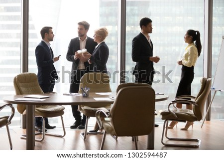 Diverse multiethnic employees standing separately talking at work, caucasian business people avoid african and asian colleagues in modern office as racial segregation discrimination prejudice concept