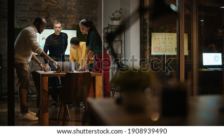 Diverse Multiethnic Team are Having a Conversation in a Meeting Room Behind Glass Walls in a Creative Office. Colleagues Lean On a Conference Table and Discuss Business, App User Interface and Design.